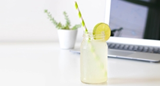 Clear drink with lime and a straw