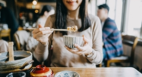 Smiling woman eating bowl of noodles with chopsticks