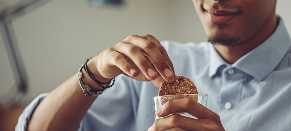 Man dunking fibre-fortified cookie into glass of milk